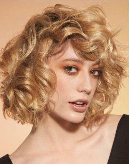 un corte de pelo corto bob con flequillo de pelo rizado y ondulado